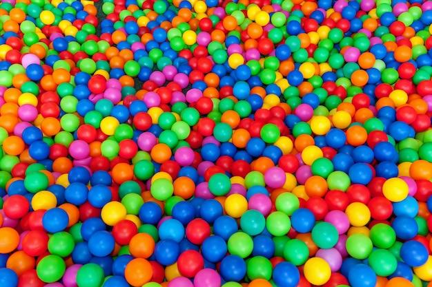 Wiele kolorowych piłek w basenie z piłeczkami na placu zabaw. piłka z kolorowymi plastikowymi kulkami w centrum rozrywki dla dzieci. basen z jasnym tłem kulek.