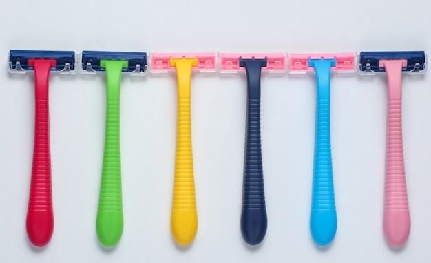 Wiele kolorowych plastikowych maszynek do golenia na białym tle.