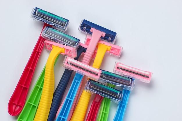 Wiele kolorowych plastikowych maszynek do golenia na białym z bliska
