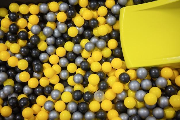 Wiele kolorowych plastikowych piłek z małego miasteczka dla dzieci. wakacje, impreza dla dzieci, sala gier, pudełko wypełnione małymi kolorowymi piłeczkami.