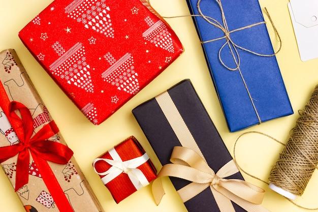 Wiele kolorowych prezentów na żółtym tle. widok z góry. pakowanie prezentów.