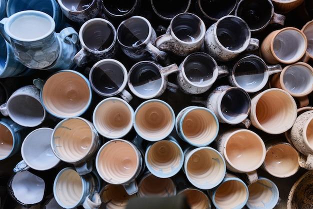 Wiele kolorowych, ręcznie robionych ceramicznych filiżanek