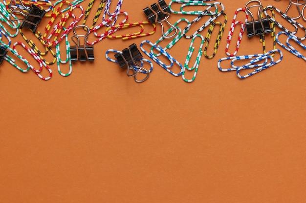 Wiele kolorowych spinaczy na brązowym tle. minimalistyczna koncepcja biura. skopiuj miejsce