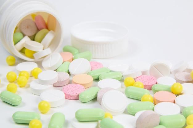 Wiele kolorowych tabletek na białym tle