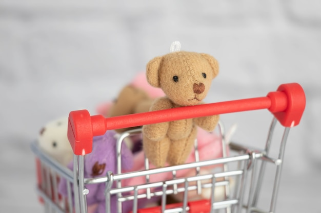 Wiele kolorowych zabawek pluszowych misiów leży w wózku spożywczym. zakupy na rynku. kupowanie prezentów na urodziny i święta.