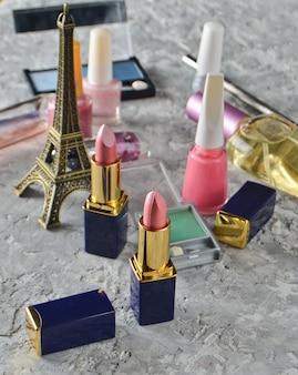 Wiele kosmetyków kobiecych do makijażu i pielęgnacji urody. lakier do paznokci, butelka perfum, cienie do makijażu, szminka, statuetka z wieży eiffla.