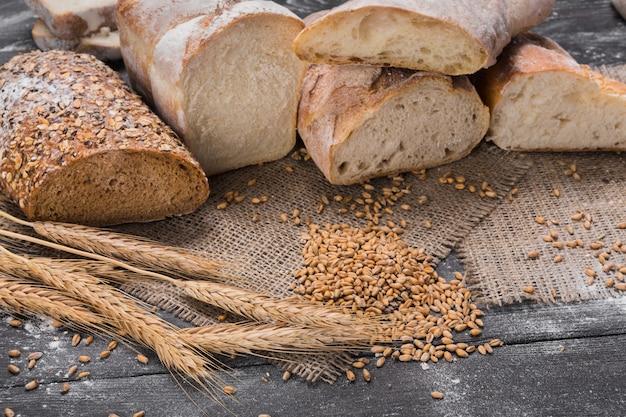 Wiele krojonego chleba. koncepcja piekarni i spożywczy. świeże, zdrowe pełnoziarniste pokrojone rodzaje żyta i białych bochenków, posypana mąką na worze i rustykalny stół z drewna, zbliżenie żywności.