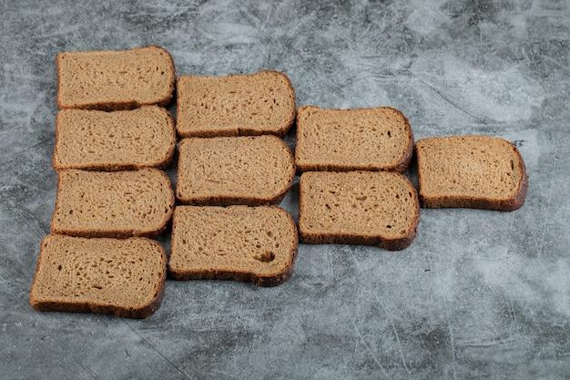 Wiele kromek ciemnego chleba na szarej powierzchni.