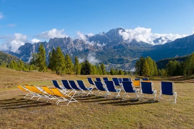 Wiele krzeseł z pięknym widokiem na cortina d'ampezzo we włoszech.