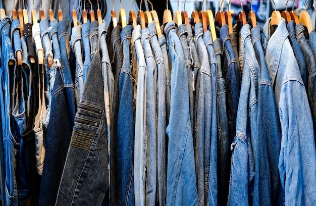Wiele kurtek jeansowych wisi na wieszaku w sklepie. rząd kurtek jeansowych w sklepie. wyprzedaż dżinsów w sklepie na ladzie. tekstura dżinsów