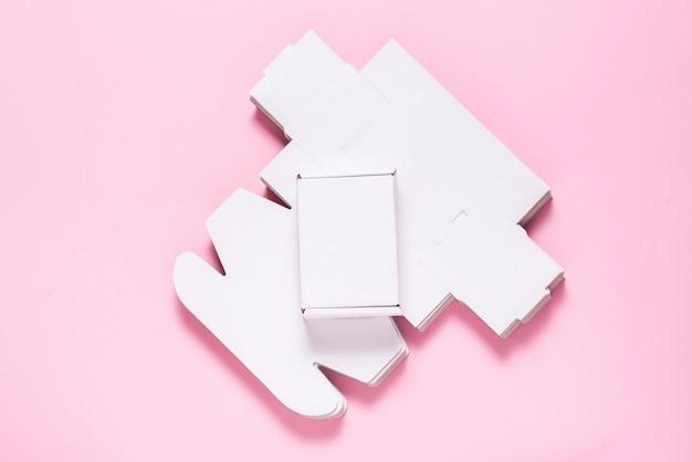 Wiele kwadratowych kartonów na różowym tle, pocięte