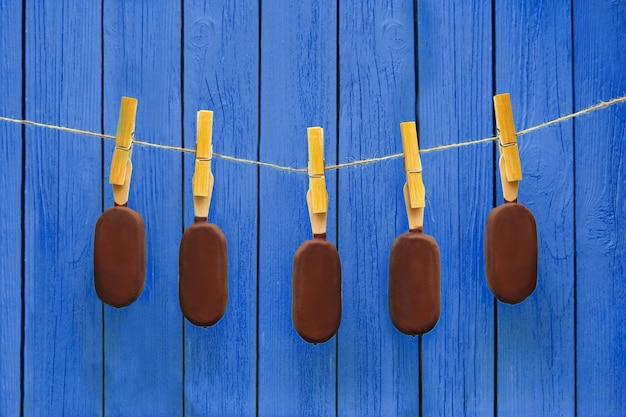 Wiele lodów czekoladowych wiszące na liny w pobliżu niebieskiego tła. gorące lato. koncepcja pysznego jedzenia
