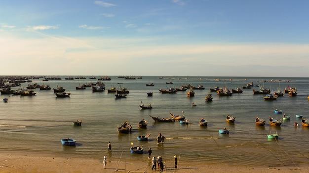Wiele łodzi rybackich unosi się w zatoce, wioska rybacka w wietnamie