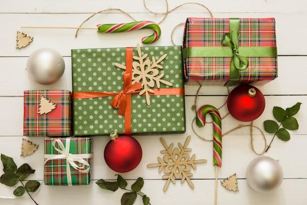 Wiele małych i dużych pudełek na prezenty na tle drewna. prezenty w kolorowym papierze ozdobione kokardkami z czerwonej wstążki i płatkami śniegu, słodycze. świąteczny stół świąteczny i nowy rok.