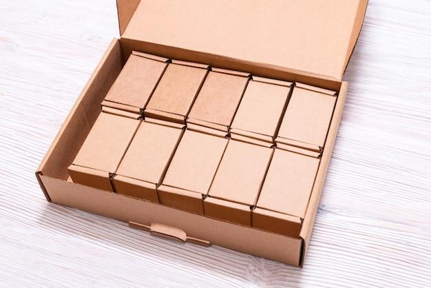 Wiele małych kartonów wewnątrz dużej skrzynki z pokrywą na drewnianym stole