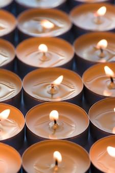 Wiele małych okrągłości płonących świec, z bliska.