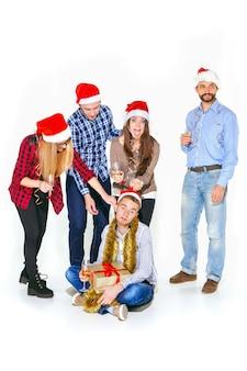 Wiele młodych kobiet i mężczyzn pije na boże narodzenie na tle białego studia