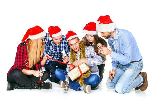 Wiele młodych kobiet i mężczyzn pije na przyjęcie świąteczne na tle białego studia z prezentem