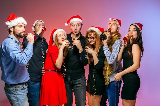 Wiele młodych kobiet i mężczyzn pije na przyjęciu bożonarodzeniowym na różowym studio