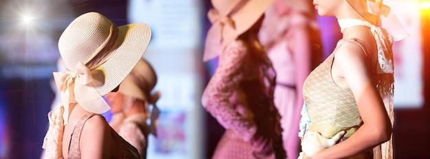 Wiele modelek stoi na rampie scenicznej jako finałowy pokaz mody, nierozpoznani ludzie z twarzą na czapkę w stylu transparentu przestrzeni kopii w tle