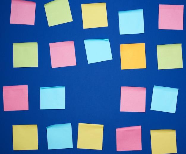 Wiele naklejonych kwadratowych wielokolorowych pustych naklejek na niebieskim tle