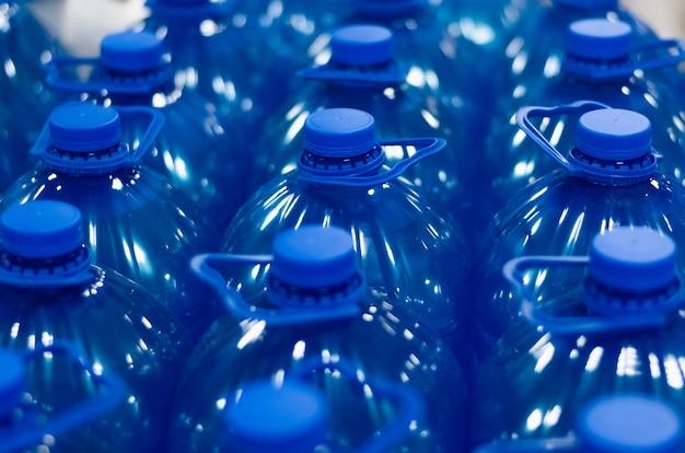 Wiele niebieskich plastikowych butelek z płynem chemicznym. grupa butelek z bliska