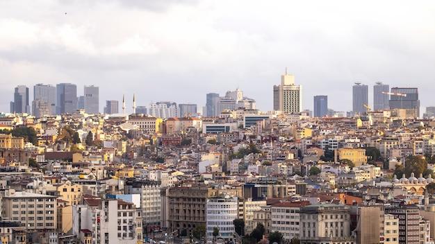 Wiele niskich budynków mieszkalnych i wysokich nowoczesnych budynków w oddali i zachmurzone niebo w stambule w turcji