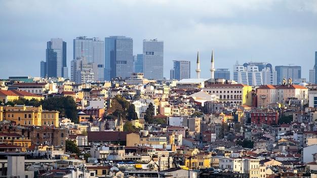 Wiele niskich budynków mieszkalnych i wysokich nowoczesnych budynków w oddali, światło słoneczne i zachmurzone niebo w stambule w turcji