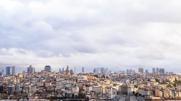 Wiele niskich budynków mieszkalnych i wysokich nowoczesnych budynków w oddali, wieża galata przy pochmurnej pogodzie stambuł, turcja
