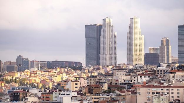 Wiele niskich budynków mieszkalnych na pierwszym planie i kilka drapaczy chmur przy pochmurnej pogodzie w stambule w turcji