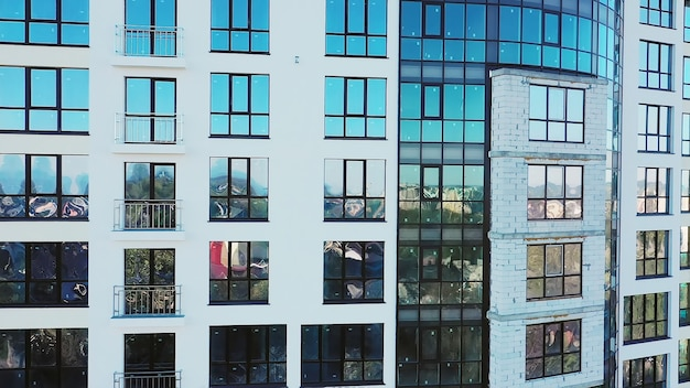 Wiele okien na nowej elewacji apartamentowca w trakcie budowy nieruchomości