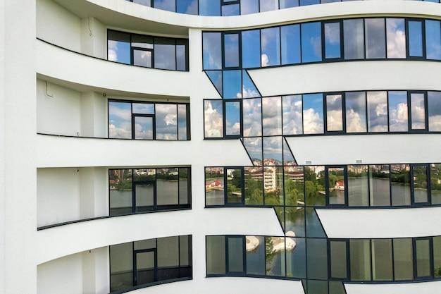 Wiele okien na nowej elewacji apartamentowca.