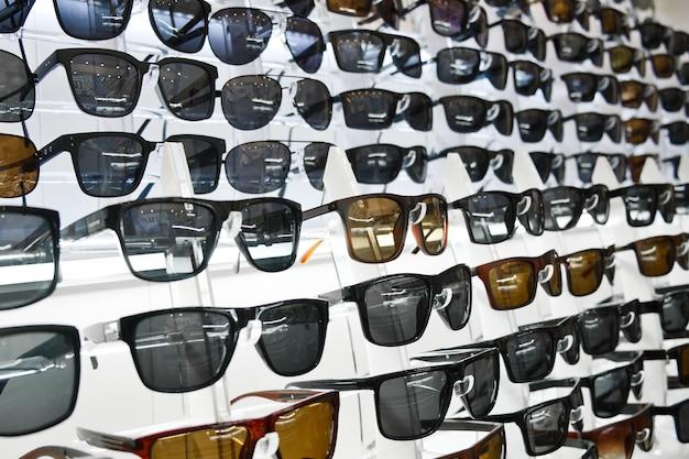 Wiele okularów przeciwsłonecznych na ladzie sklepu optycznego. asortyment plastikowych okularów przeciwsłonecznych.