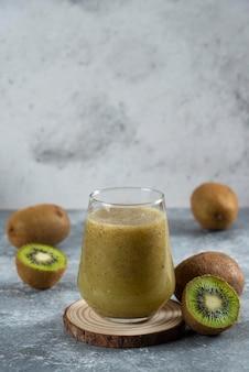Wiele owoców kiwi popijając szklanką soku.