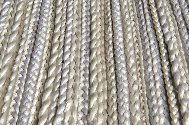 Wiele plecionek z włókien syntetycznych o różnych splotach. tekstura, tło. materiał fryzjerski - kanekalon, używany do tkania syntetycznych warkoczy i peruk.