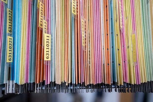 Wiele plików jest ułożonych w szafce biurowej.