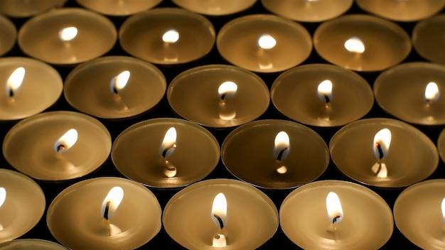 Wiele płonących okrągłych małych świec z odblaskami płonie w ciemności.