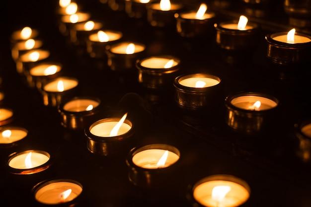 Wiele Płonących świec Kościelnych W Rzędach Premium Zdjęcia