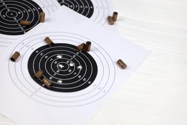 Wiele pocisków z tarczami strzeleckimi na białym stole w wielokącie strzelnicy. szkolenie w zakresie celowania i celności strzelania