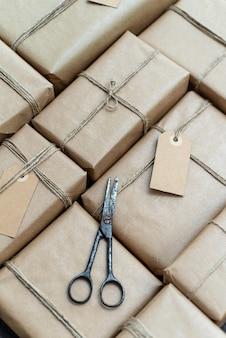 Wiele prezentów zawiniętych w papier z recyklingu z etykietami i zardzewiałymi nożyczkami