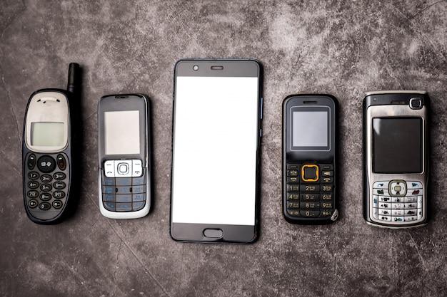 Wiele przestarzałych telefonów komórkowych i smartfona na tle grunge.