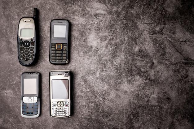 Wiele przestarzałych telefonów komórkowych na tle grunge.