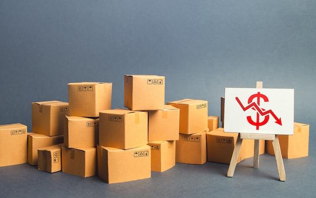 Wiele pudełek kartonowych i sztalug z czerwoną strzałką dolara w dół.