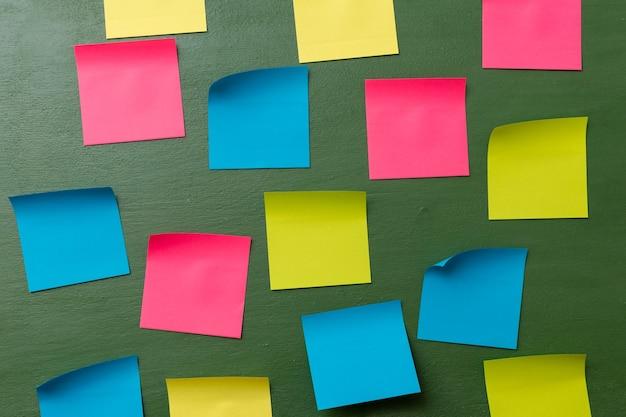 Wiele pustych kolorowych naklejek pamięciowych na ciemnozielonym tle koncepcja biznesowa zajętego dnia