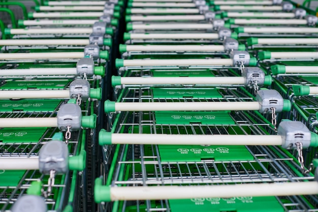 Wiele pustych zielonych koszyków na zakupy w rzędzie