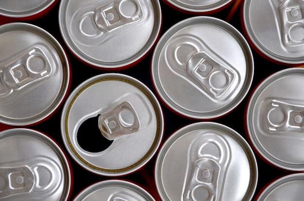 Wiele puszek napojów gazowanych lub napojów energetycznych. wiele puszek pochodzących z recyklingu wykonanych z aluminium i przygotowywanych do ponownej produkcji.