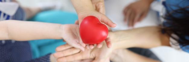 Wiele rąk kobiet, mężczyzn i dzieci, jedna nad drugą, trzyma serce.