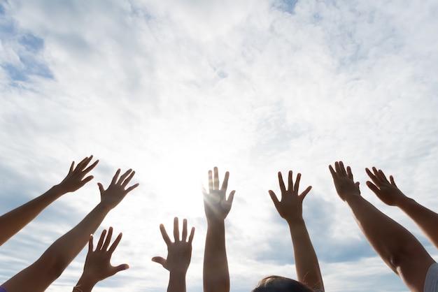 Wiele rąk podniosło się na tle błękitnego nieba. przyjaźń, koncepcja pracy zespołowej
