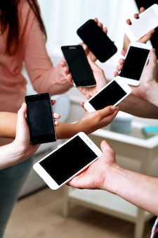 Wiele rąk trzymając telefony komórkowe z bliska