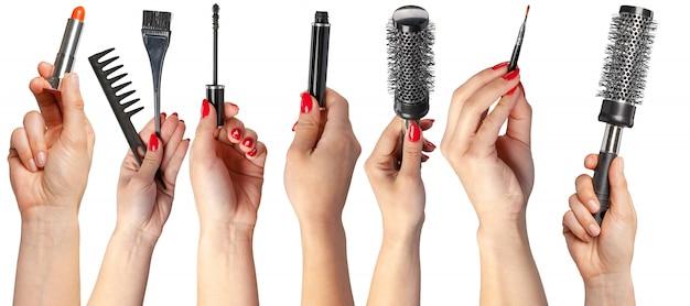 Wiele rąk z produktami do makijażu